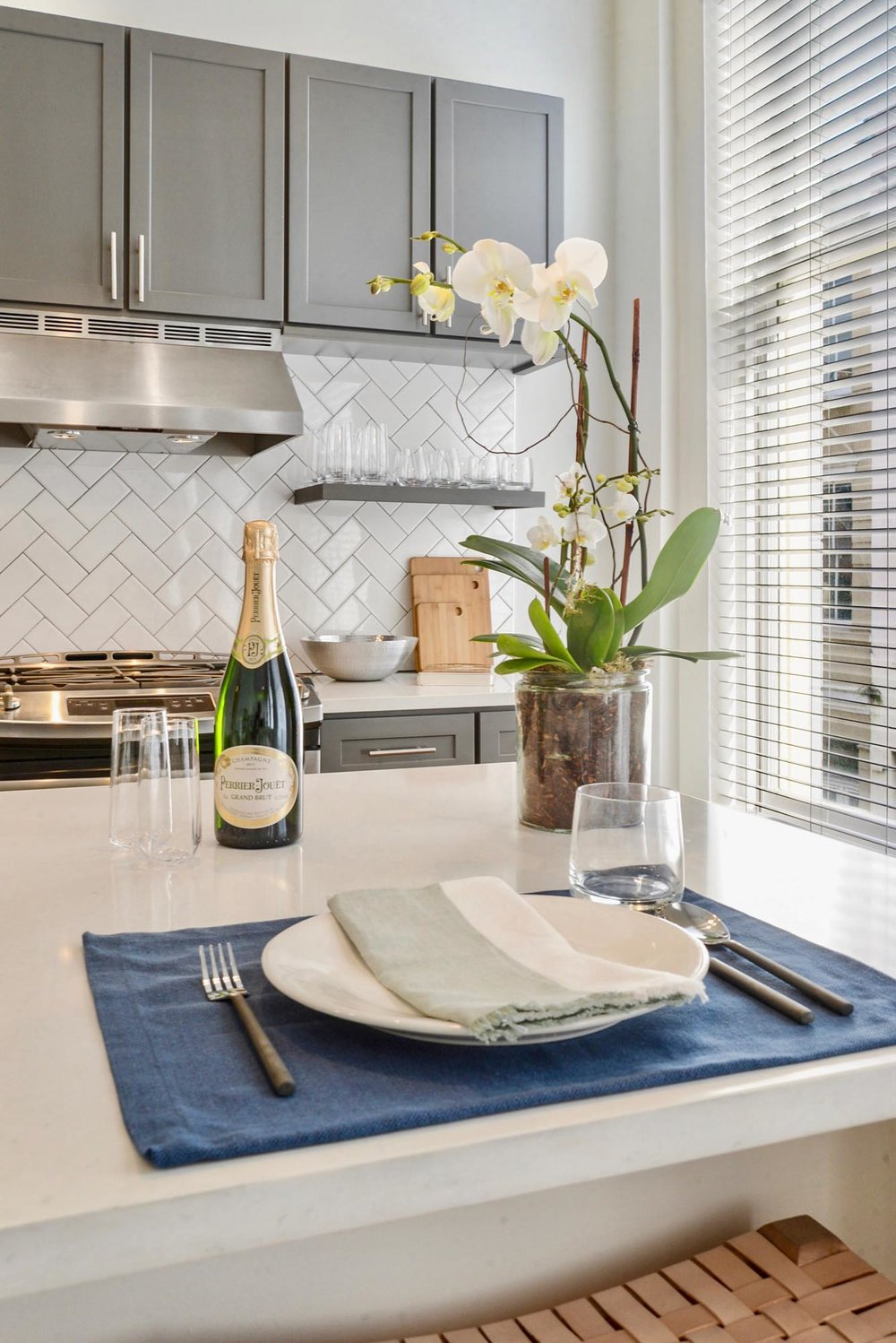 White kitchen island with place setting and flowers