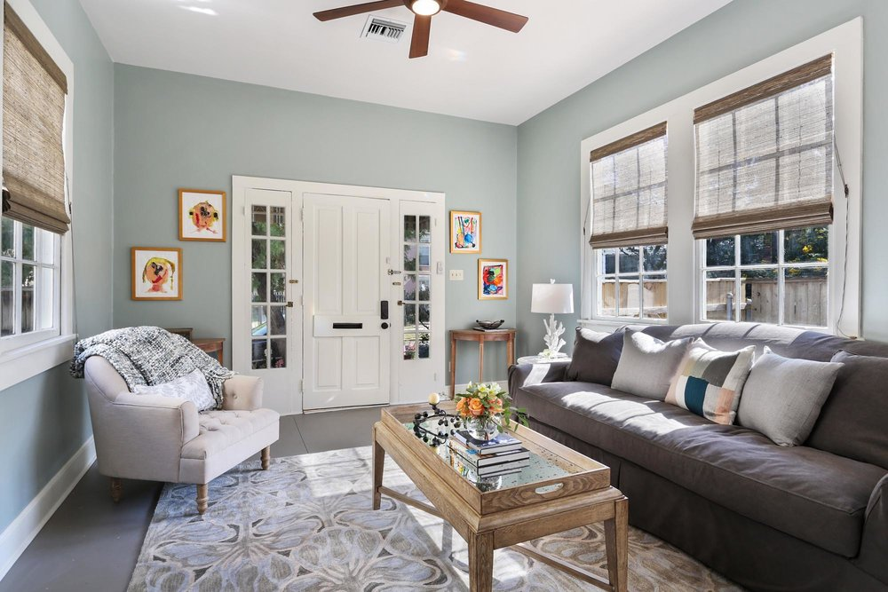 Comfortable seating area with colorful small paintings on the wall