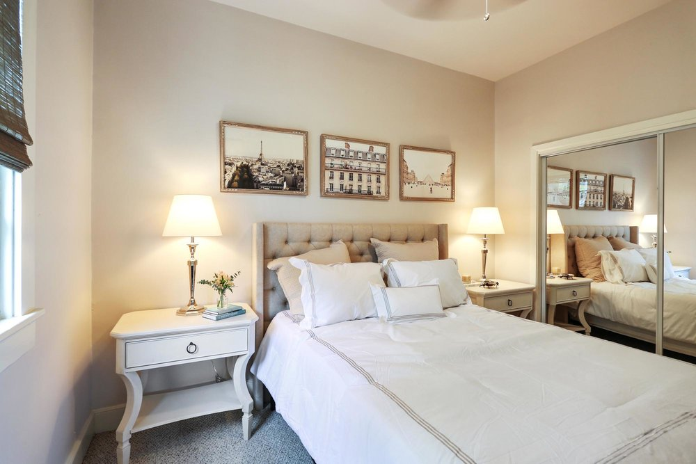 Bedroom with soft white colored walls and sepia photographs of France hanging above bed