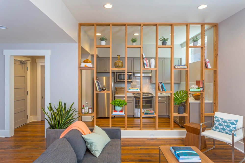 Modern sitting area with floor to ceiling open wall with wood partition bookcase