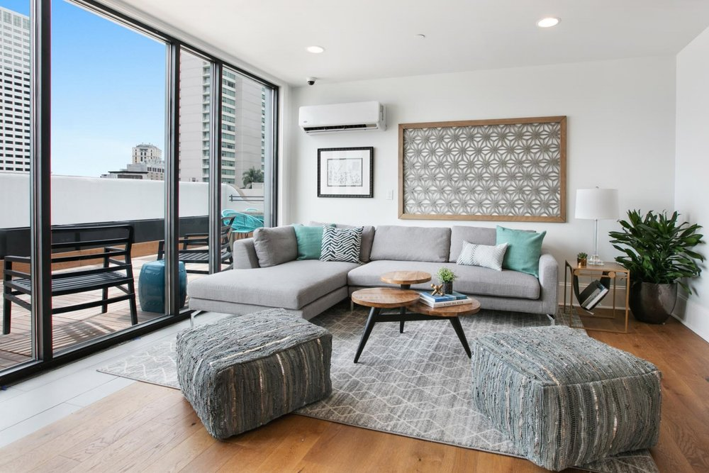 Brightly lit lounge space with floor to ceiling windows and ample seating