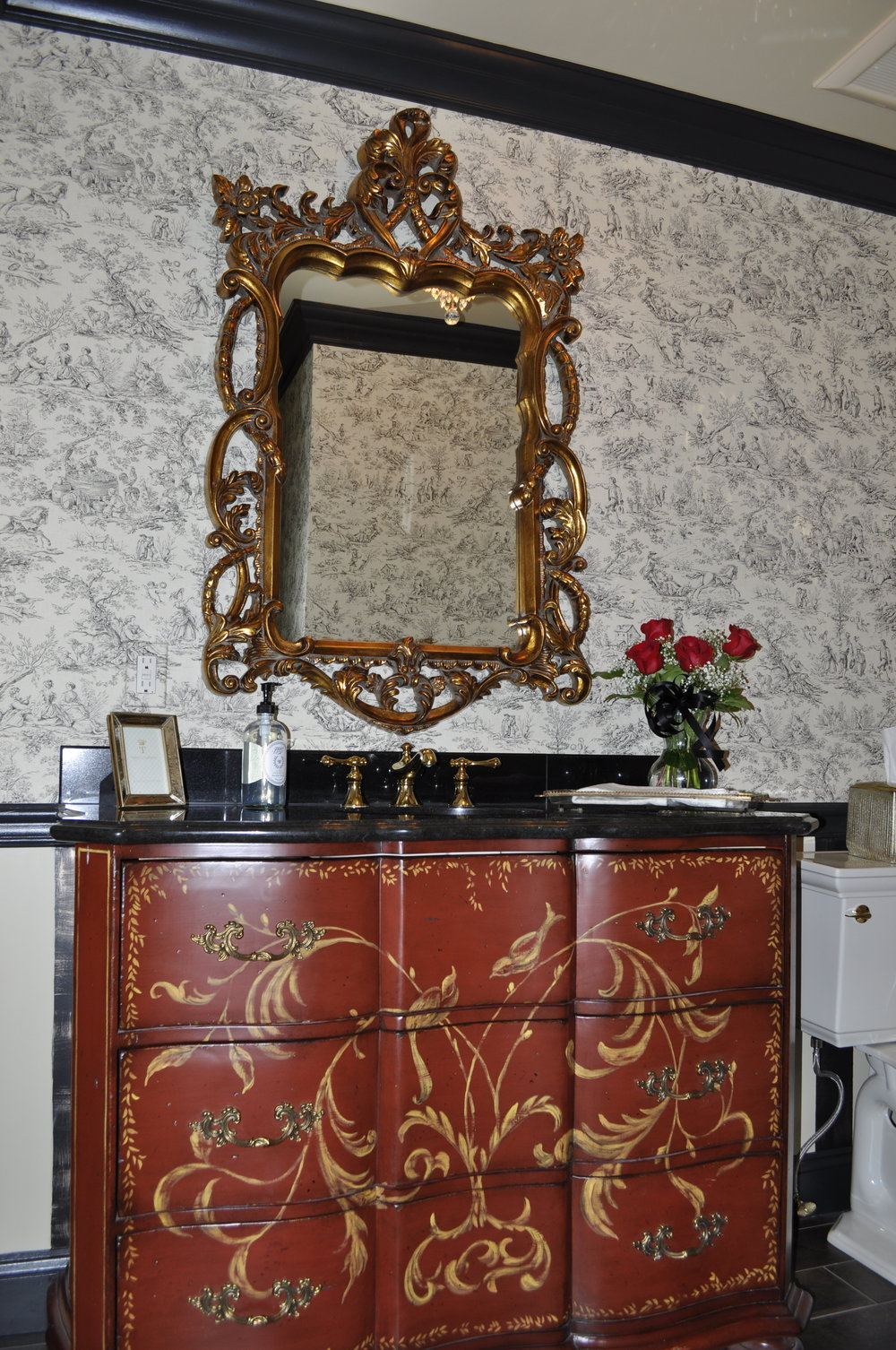 After:  The converted chest and the simple black granite are the perfect pairing. The gold, hand-painted scroll work complements the ornate mirror while beautifully balancing the toile wallpaper. The chic accessories round out the design. No detail is overlooked!