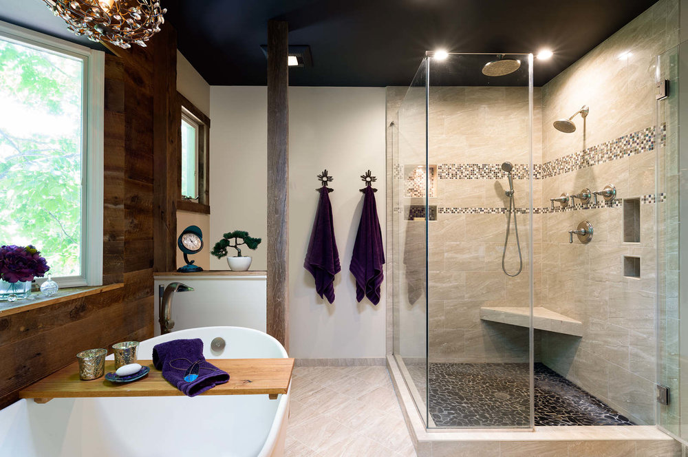 After  - Flat river rock was chosen for the flooring in the shower to keep the look clean and organic. A custom bench seat on an angle takes advantage of every inch of space we had.