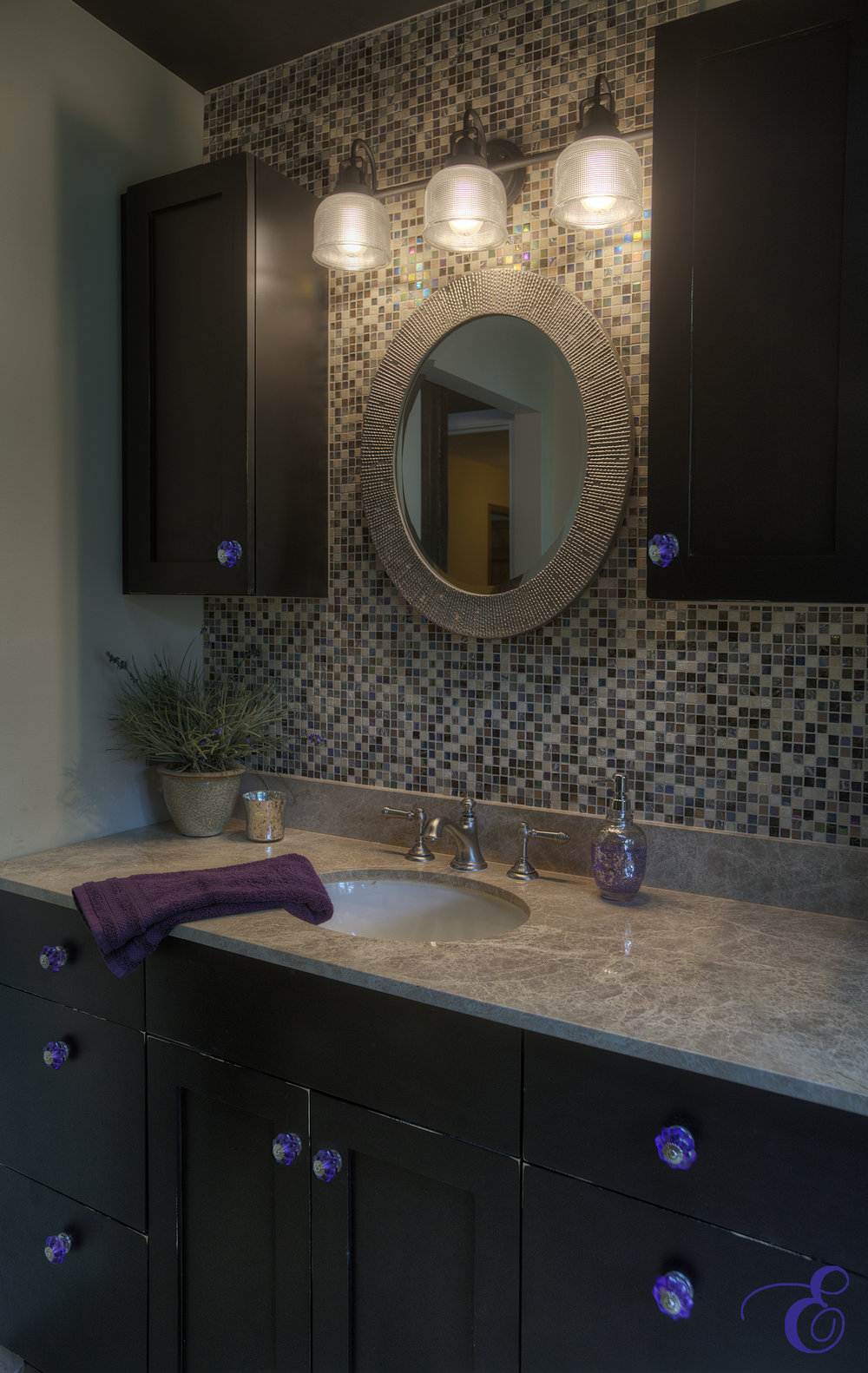 Distressed black cabinets with purple glass knobs against a tile wall