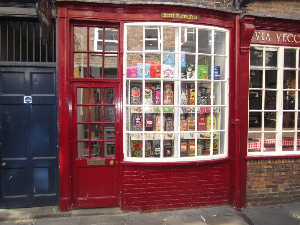 A charming red storefront in London. It looks like the candy store in  Harry Potter !