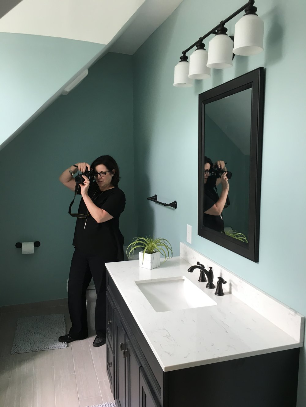 We used black in this bathroom to add a little edge to the light, soothing space. Christine is hard at work photographing our design.
