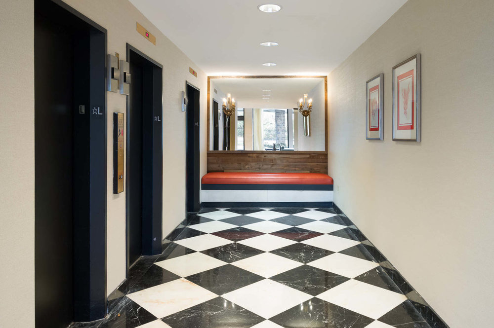 By Ella Design Group. Pops of orange look chic with black and white floors in this commercial lobby we designed.