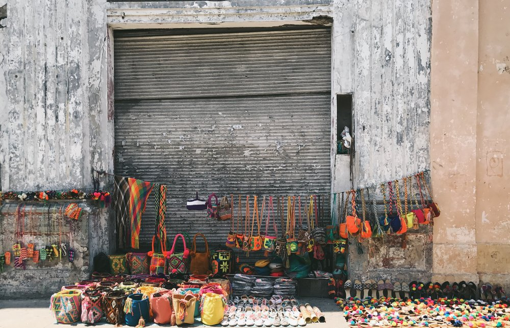 COLONIAL CONTRAST |  The streets are lined with bright, bold handmade goods arranged against muted, crumbling walls