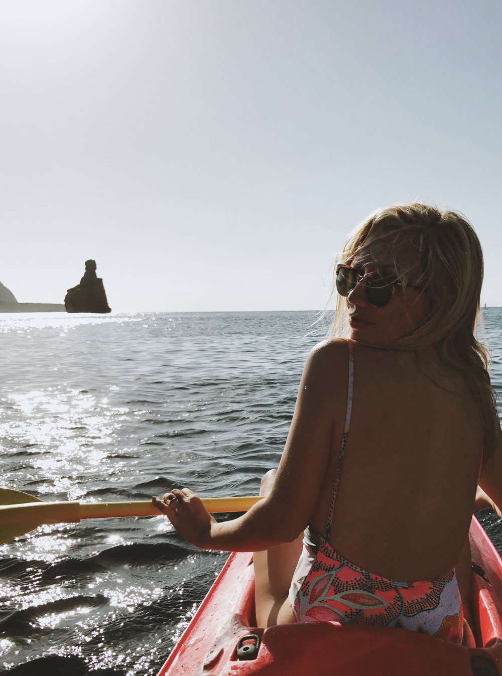 Kayaking in Benirrás Bay |  known for its drum circle Sundays and epic sunsets, Cala Benirrás features an array of restaurants offering to-die-for paella and killer cocktails. swimsuit:  M  ara Hoffman , shades:  persol