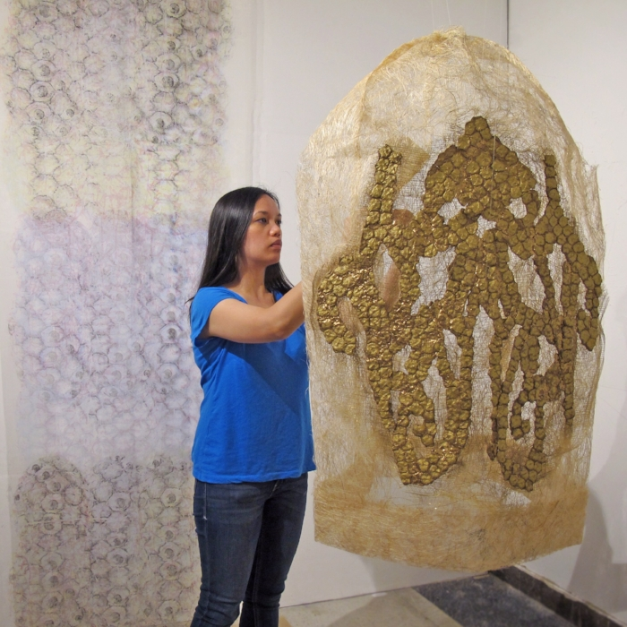 Rea in her studio   with her sculpture  After Maria Clara's Piña Fiber Sleeve,  ARTslant's 2014 Mixed Media Showcase Juried Winner