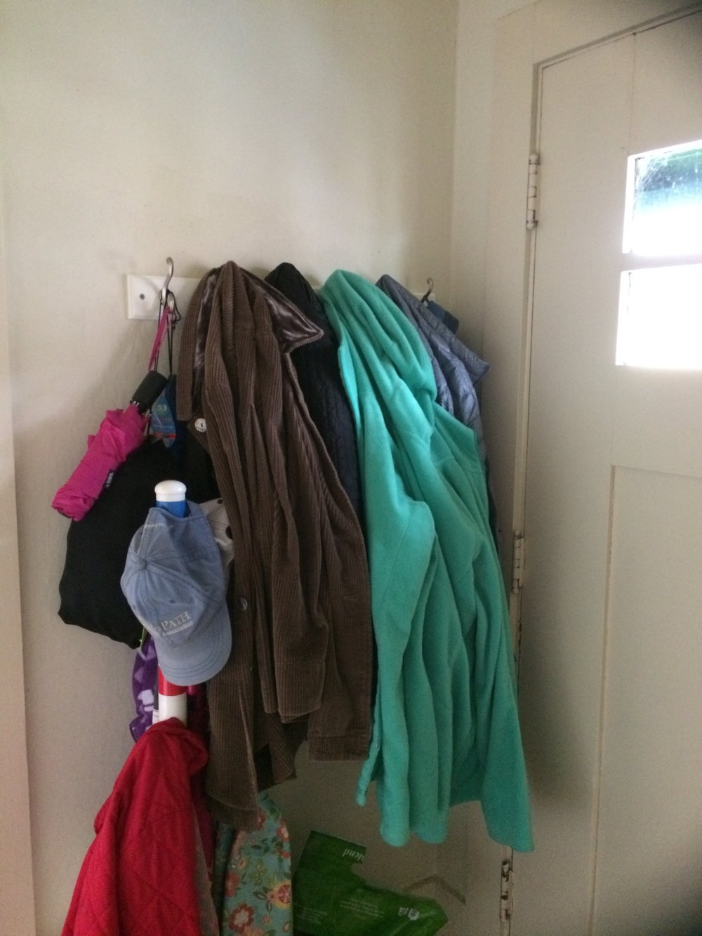 Coat rack with inaccessible coats a few layers deep.