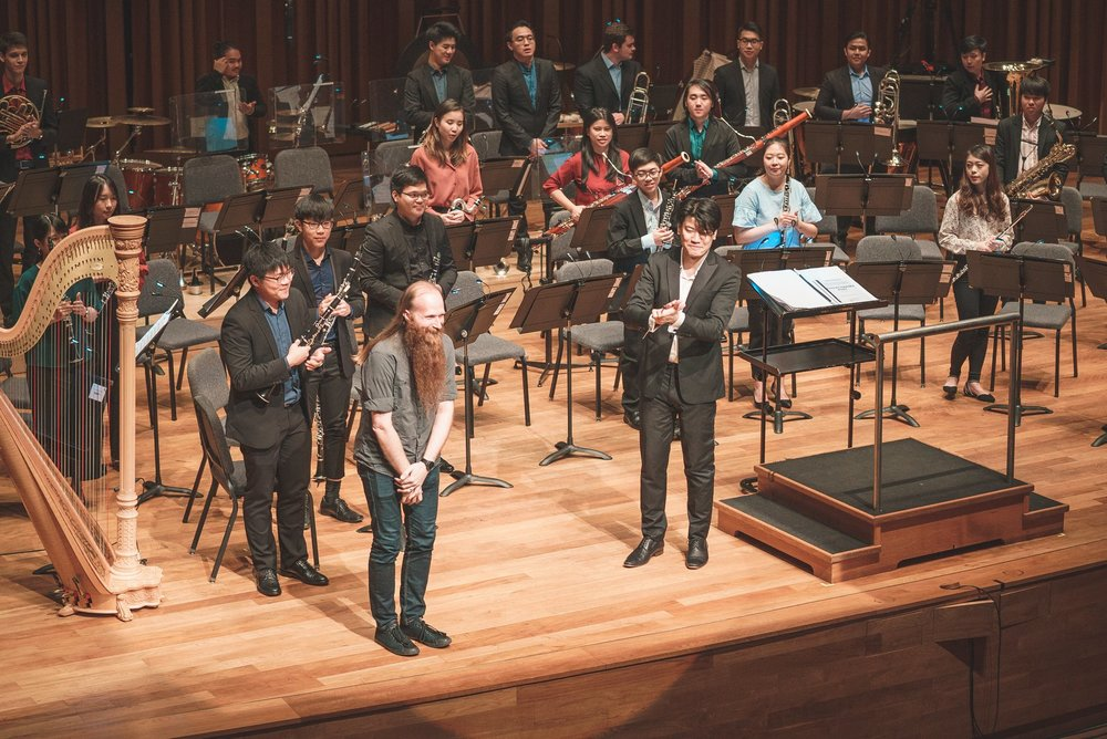 "The YST Wind Consort, conductor Chong Wailun (MMus Year 2) and YST Composition faculty Asst Prof Nick Omiccioli giving a bow, after a performance of Asst Prof Omiccioli's well-received ""Fuse""."