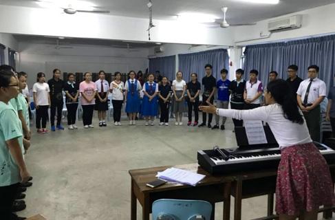 Alice conducting a choir rehearsal.