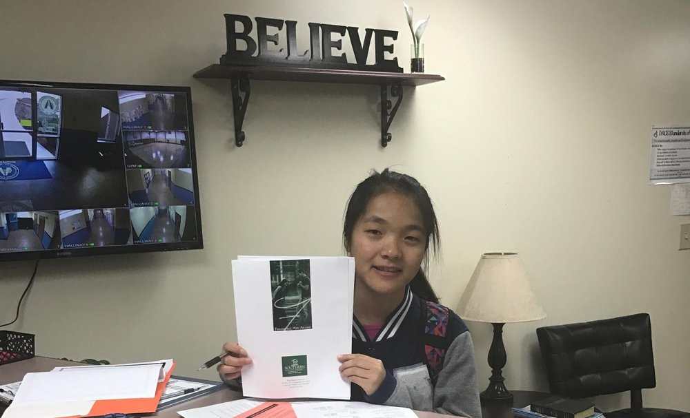 February 17, 2017 - Niang Muang proudly holds paperwork confirming that she has been awarded a scholarship to attend Southern Adventist University as she continues towards her goal of becoming a dentist. Nia richly deserves the scholarship award as she has worked long and hard to achieve scholastic excellence (4.0 GPA through high school at AAA). Over the past six years that she has been a F.R.E.E. sponsored refugee student at DACS/AAA. We expect great things from her at Southern this coming school year, having just graduated from AAA in May 2017.  (See next photo below.)