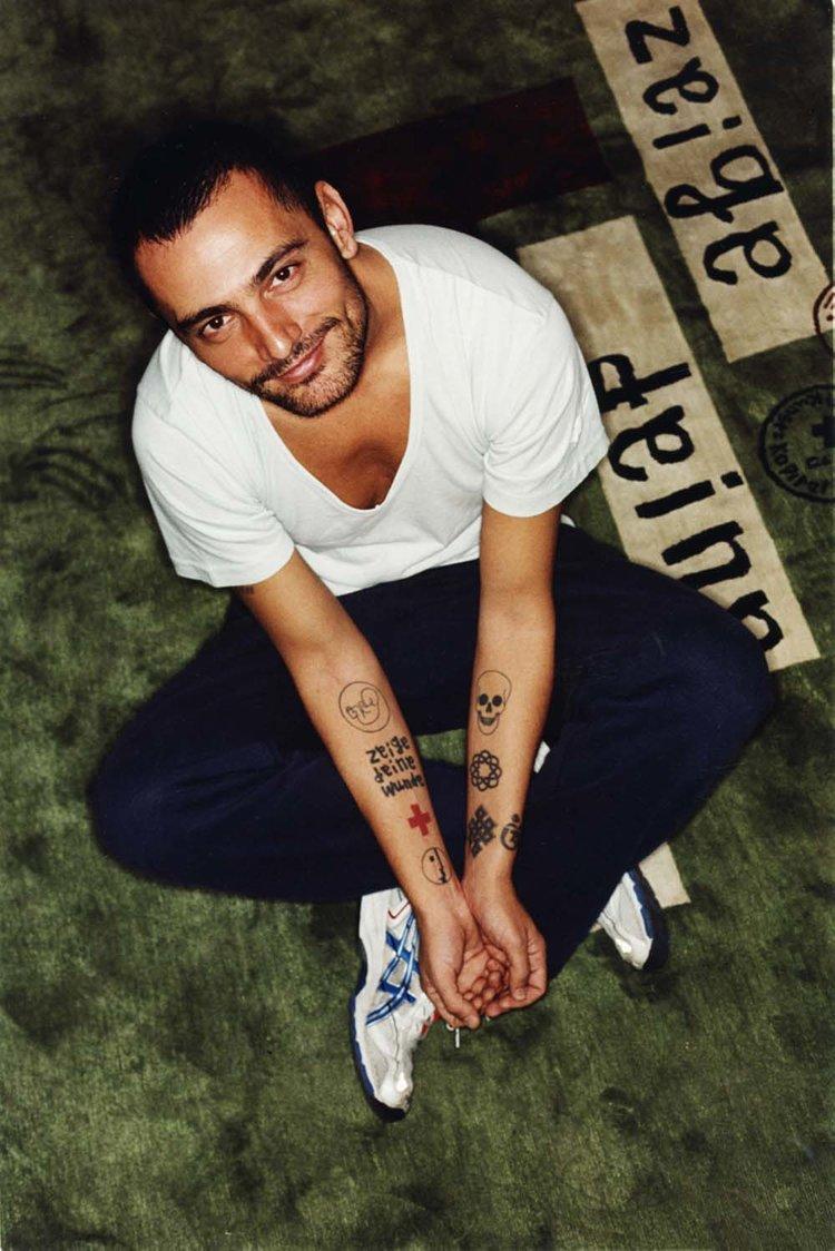 Lo stilista spagnolo David Delfin ritratto per Flair è seduto sul tappeto che riproduce i suoi tatuaggi.