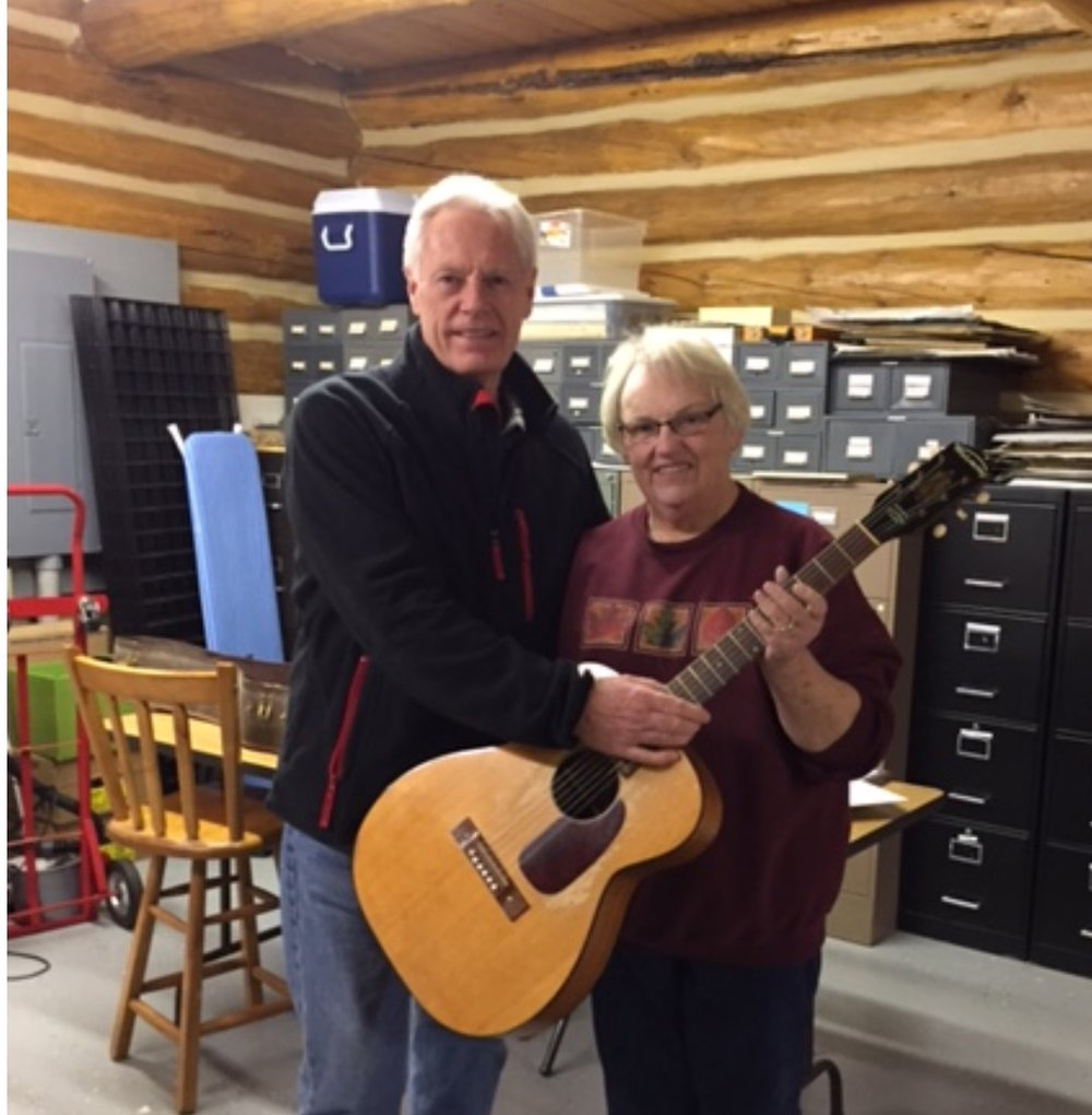 Handing off the Ted Mack audition guitar to Solveig at the Norman County Historical Society in Ada, Minnesota.