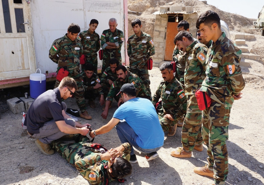 AN FAI VOLUNTEER shows Peshmerga how to apply a tourniquet at a base at Hawija, Iraq. (Photo credit:SETH J. FRANTZMAN)