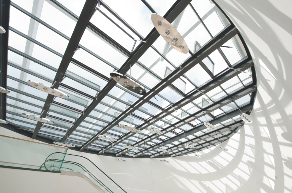 High performance skylights can provide many functions from aesthetic to practical. The PR-60 system from LAMILUX provides a daylight with a custom shape, motorized ventilation and integrates artificial lights