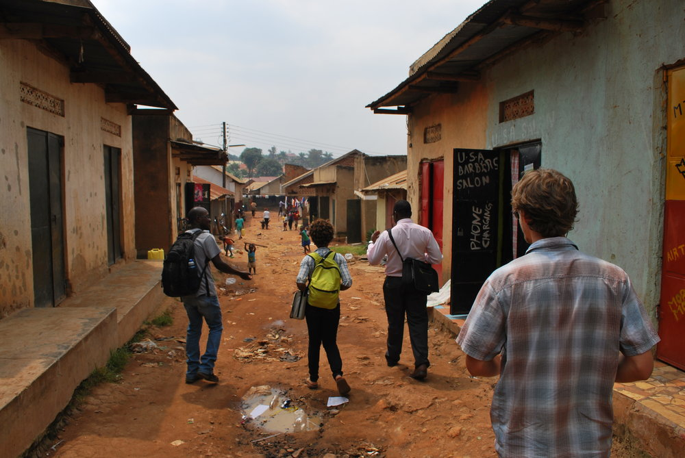 Field workers enter a street near downtown Kampala to recruit participants for a study.