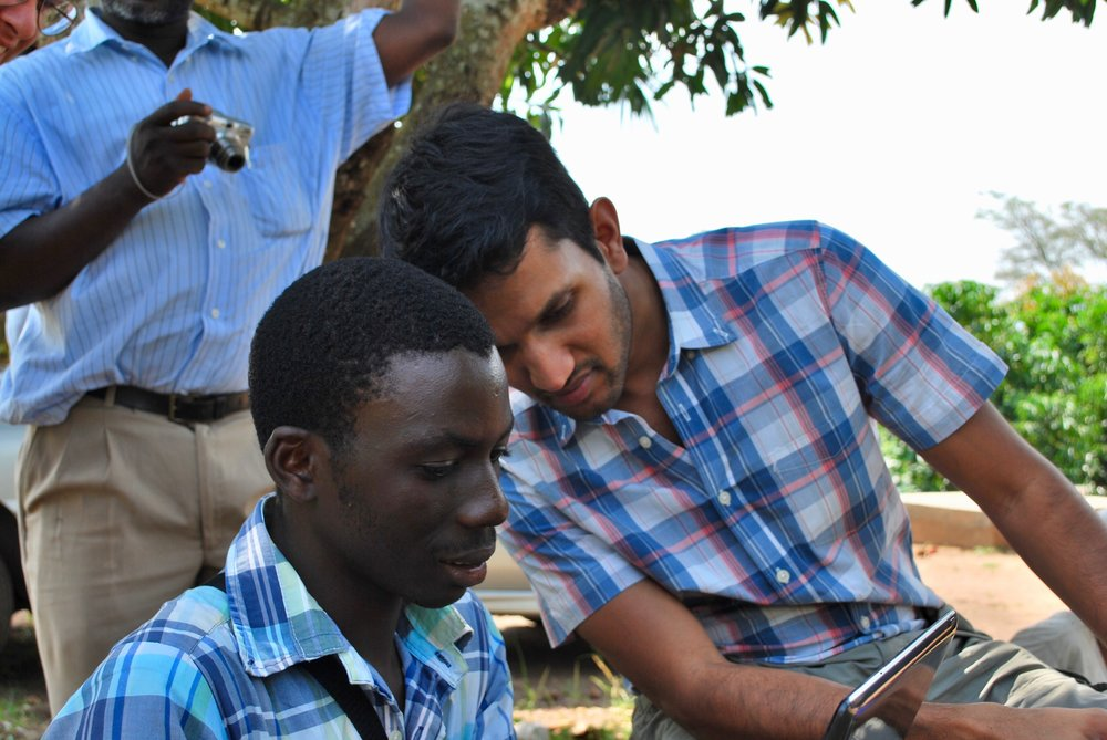 Dr. Trishul Siddharthan supervises field worker Denis while collecting data in Nakaseke.