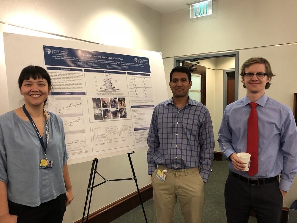 Suzy, Trishul, and Matt in front of a poster describing the research that has come from the Grand South consortium – a collection of five population-based studies covering sites in Peru, Argentina, Chile, Uruguay, Uganda, and Bangladesh.
