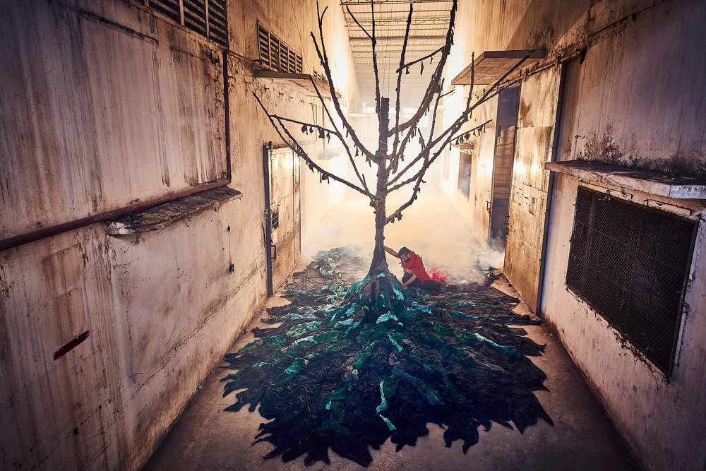 An abandoned garment factory in Phnom Penh is reclaimed by artists in a haunting exhibition that depicts the impact of the fashion industry on the environment. Photo credit Von Wong & Laura Francois, Clothing the Loop