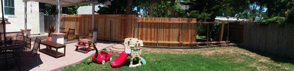 Backside of 95 ft. cedar picket fence
