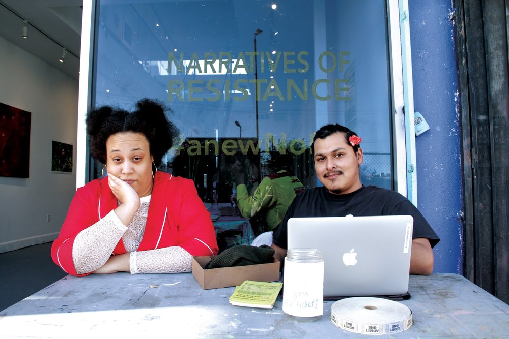 Misabel Belcher (left) and Co-Editor of the Narratives of Resistance Magazine (NoRM) Alfredo Alvarado (right) are posted outside of Leiminspace Gallery during the NoRM release show, in Chinatown April 20, 2018. Photo by: Eve Moreno-Luz