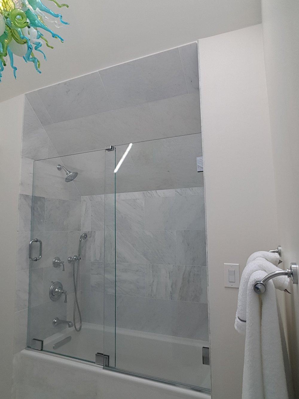 Headerless glass sliding shower door and panel