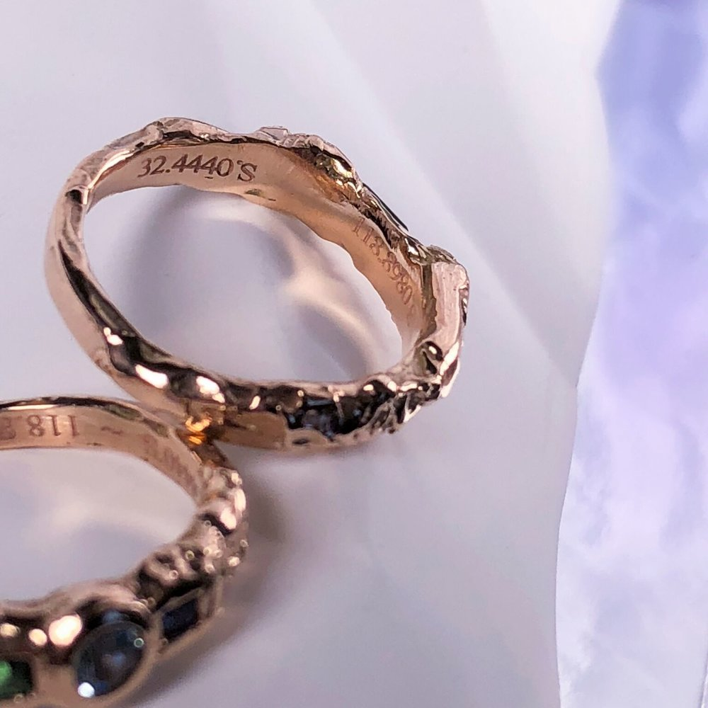 Close up of co-ordinates engraving on Bohdi & Olivia's elopement rings.