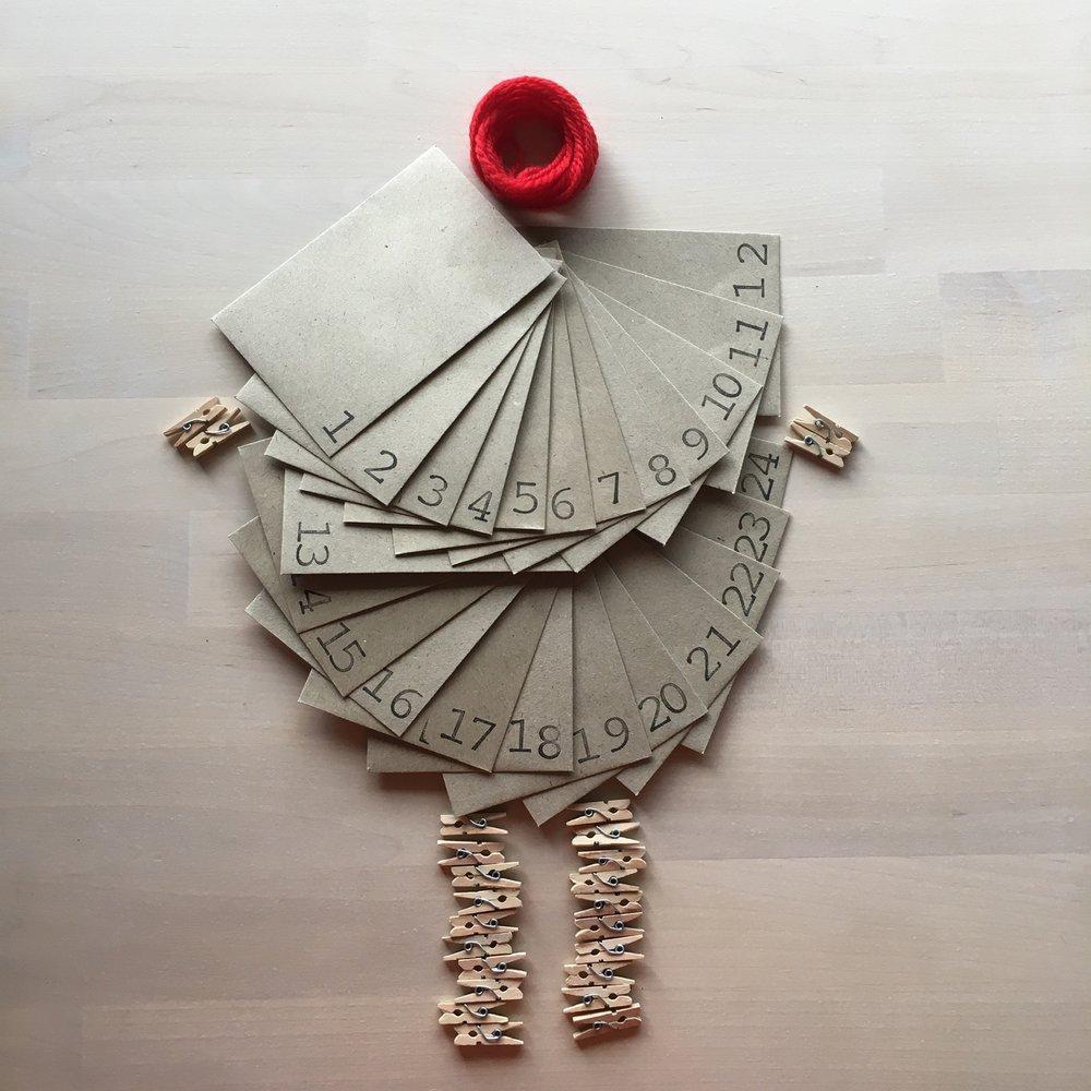Kirjekuorissa käsinleimatut numerot, villalankaa ripustusta varten, ja pieniä pyykkipoikia.