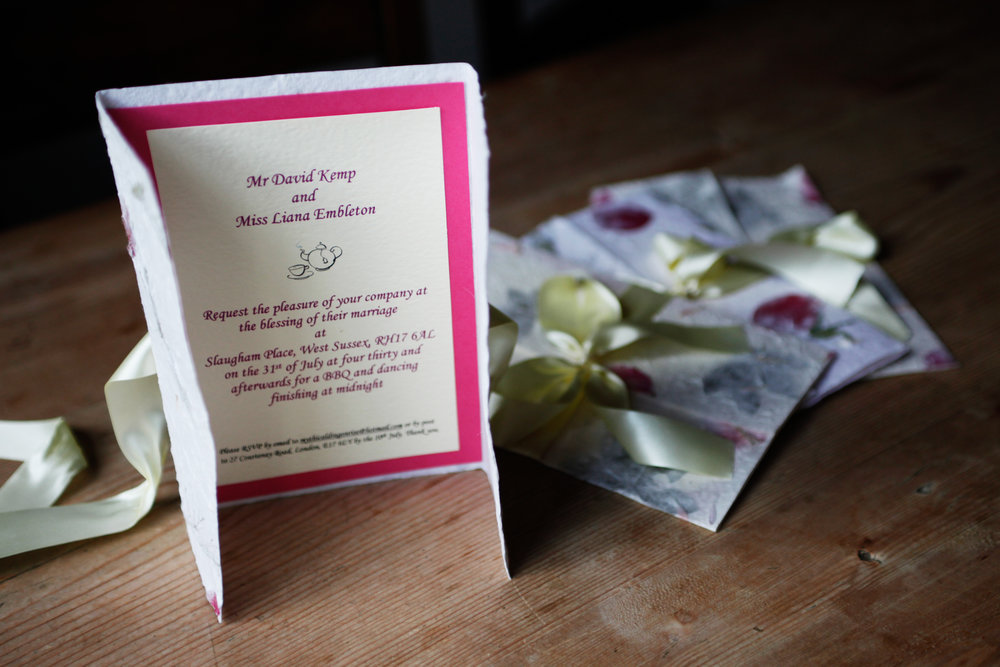 Invitation cards on a wooden table top can give a touch of colour and elegance to a wedding album.