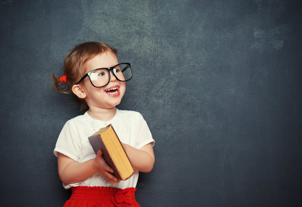 Young girl holding book and smiling happily