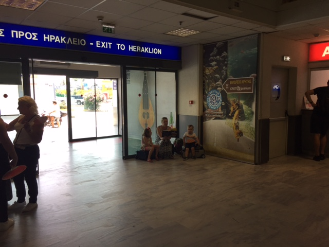 That's me in the corner of the Heraklion airport, reading the same books over and over again to try and entertain the kids while we waited for our rental car.