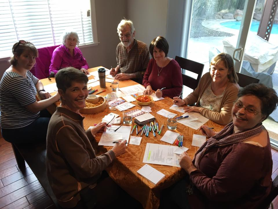 Members of the CA-3 team write postcards to voters.