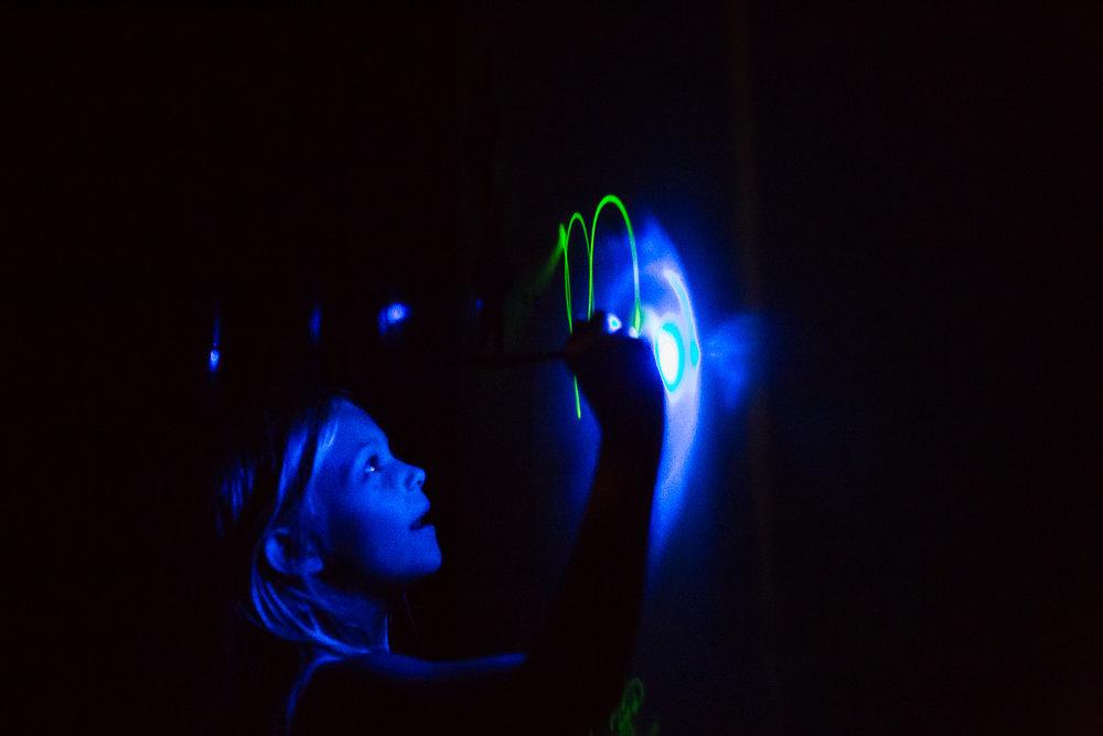 Girl writing on glow in the dark wall