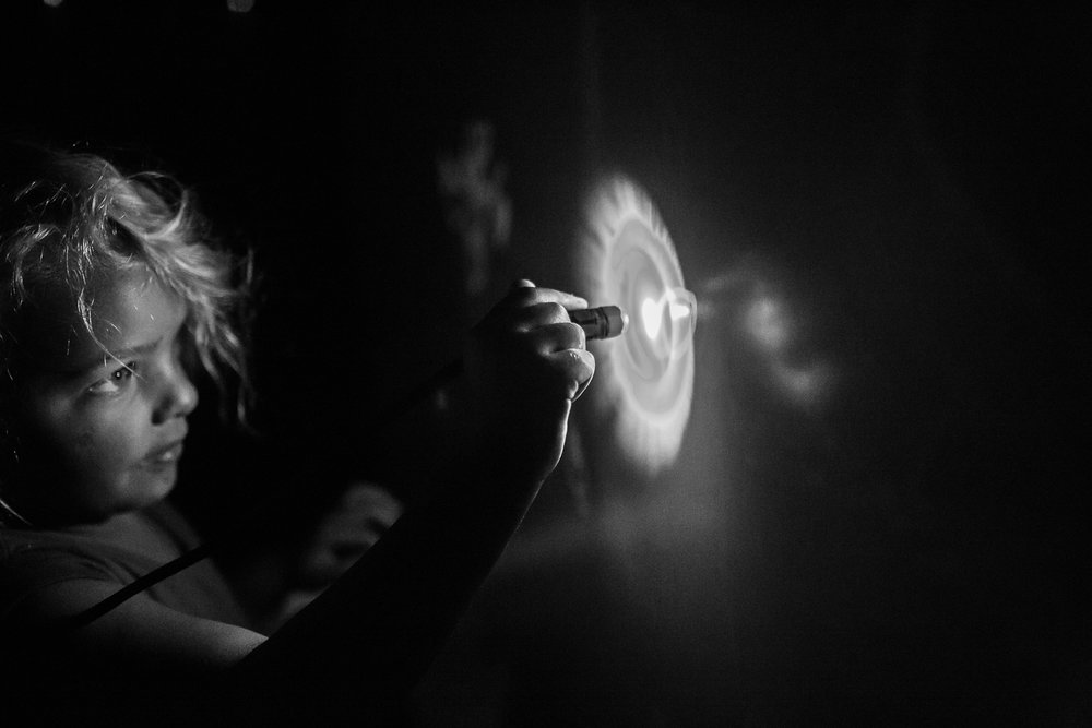 Black and white image of girl writing on glow in the dark wall