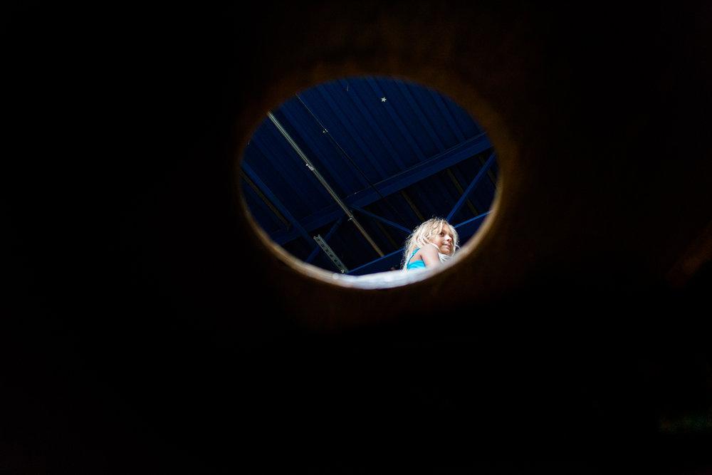 Head of girl seen through circular cutout