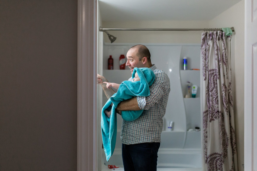 father holding baby wrapped in towel after bath
