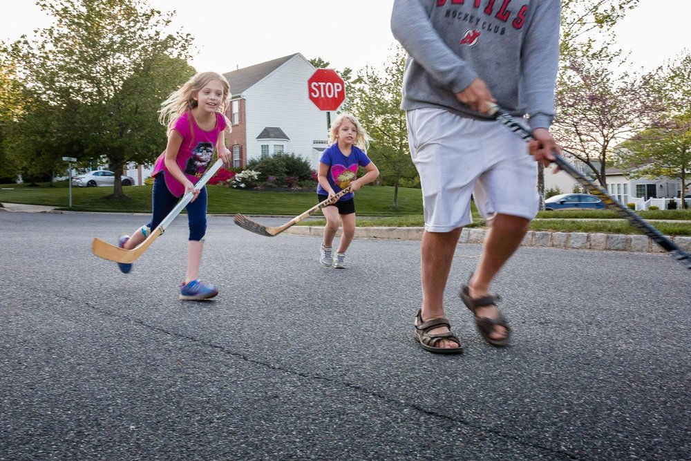 Lifestyle image of two girls running after dad with hockey sticks