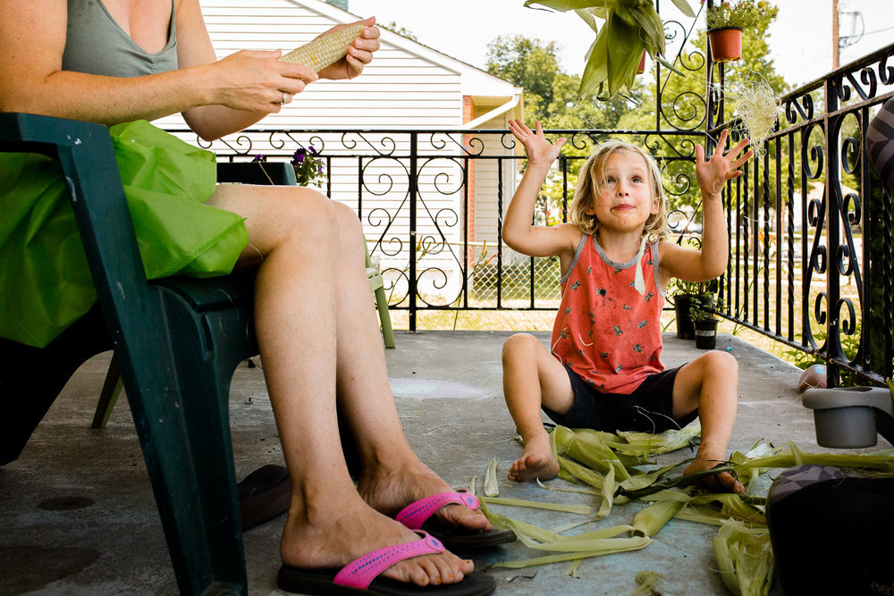 Boy throwing corn husks in the air while sitting on porch with mom.