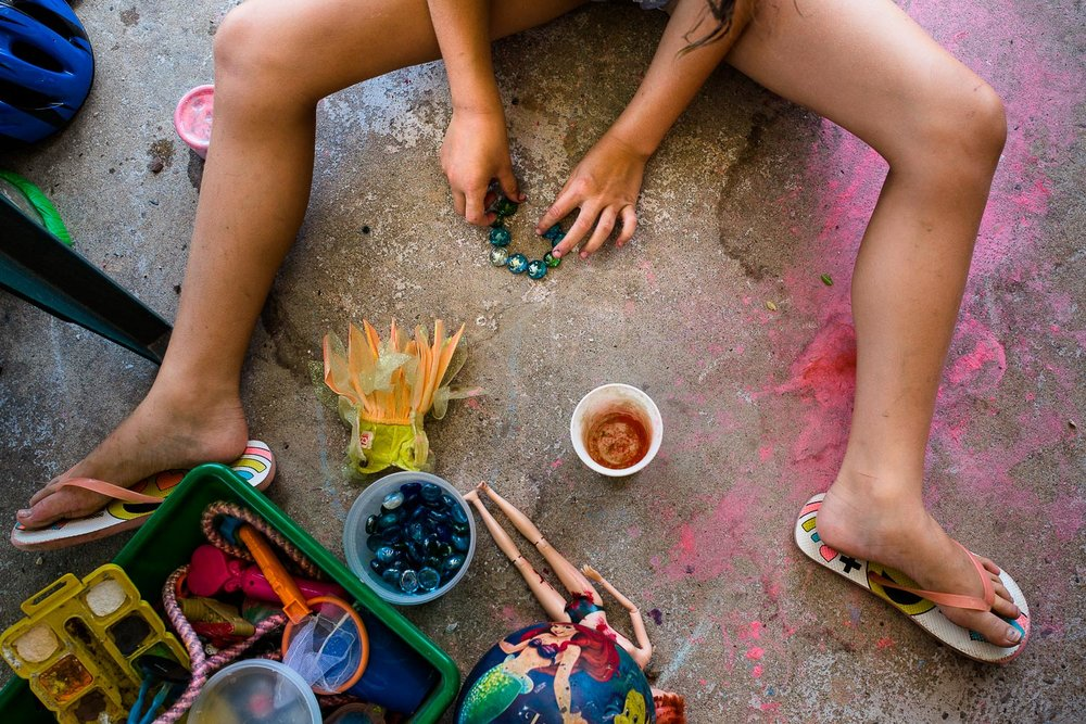 Photo of girls' hands and legs while she plays on porch with gems and chalk and toys.