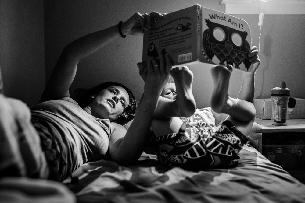 Black and white photo of mom reading to son on bed.