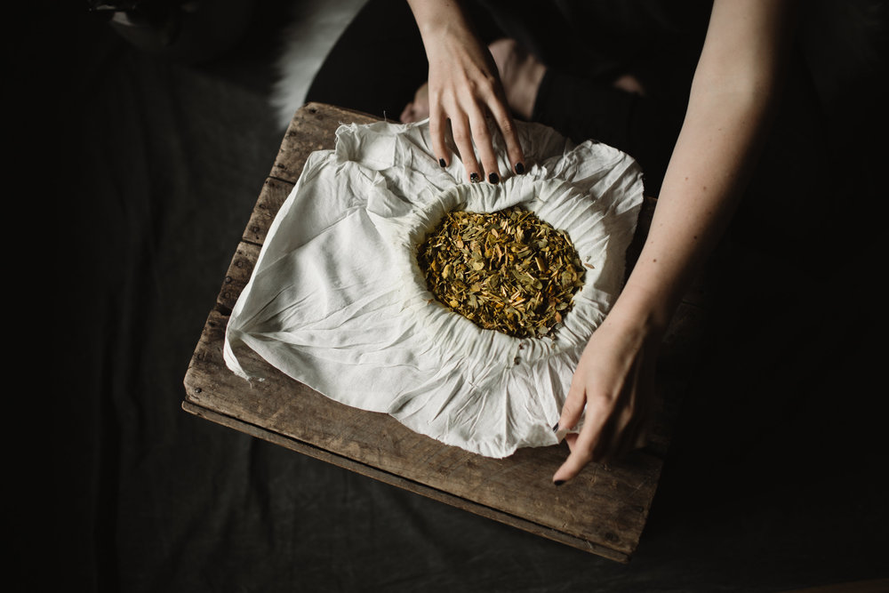 Preparing Thai herbal compress to be steamed and applied to the body