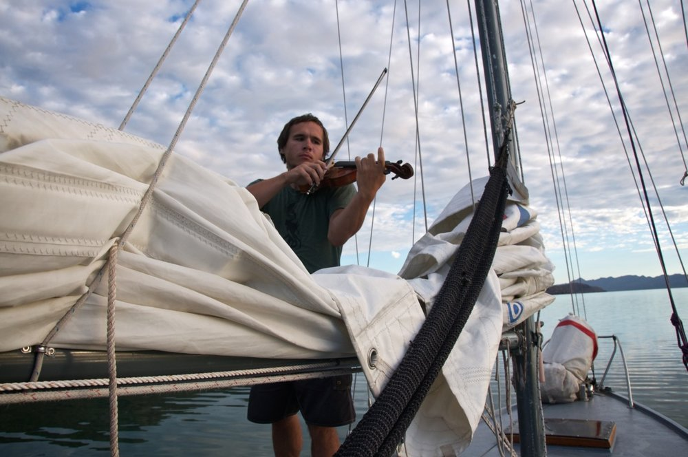 John Bridenbeck plays the violin on the deck of  Rosalita.