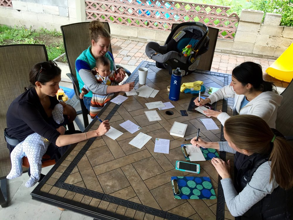 Claire Trapp, Jessica Arce-Larreta, Silvia Catten, and Brienne Henderson write postcards to their representatives in Millcreek, UT. (Andrea Smardon)