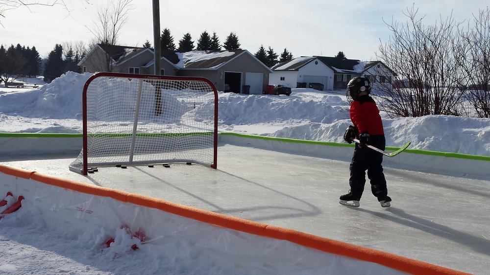 Kid Skating On A Backyard Hockey Rink.