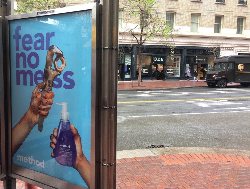 L'abribus fait la réclame de  method  (méthode), une marque de détergents respectueux de l'environnement et, de l'autre côté de la rue, on distingue la boutique d'un opticien qui s'appelle  see  (voir).