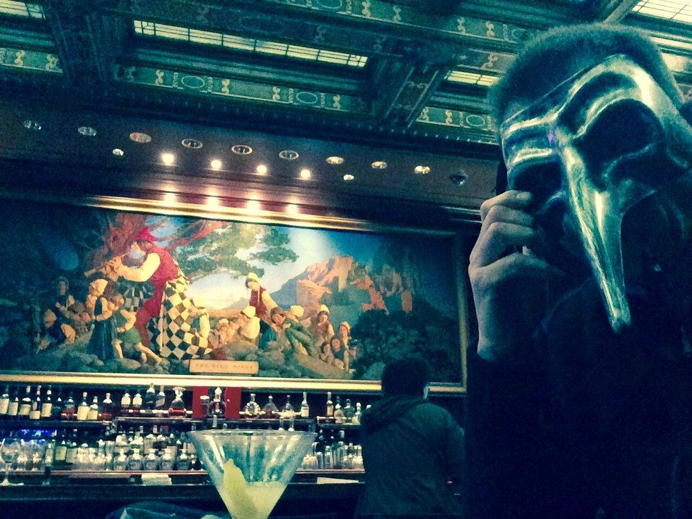 Derrière moi (et mon masque vénitien de docteur de la peste), au bar du  Palace , une fresque illustrant le conte du Joueur de flûte de Hamelin