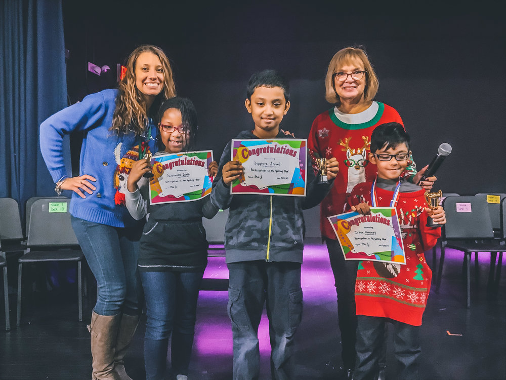 The top three 2nd grade spellers share the limelight with Ms. J and Ms. Mamara.
